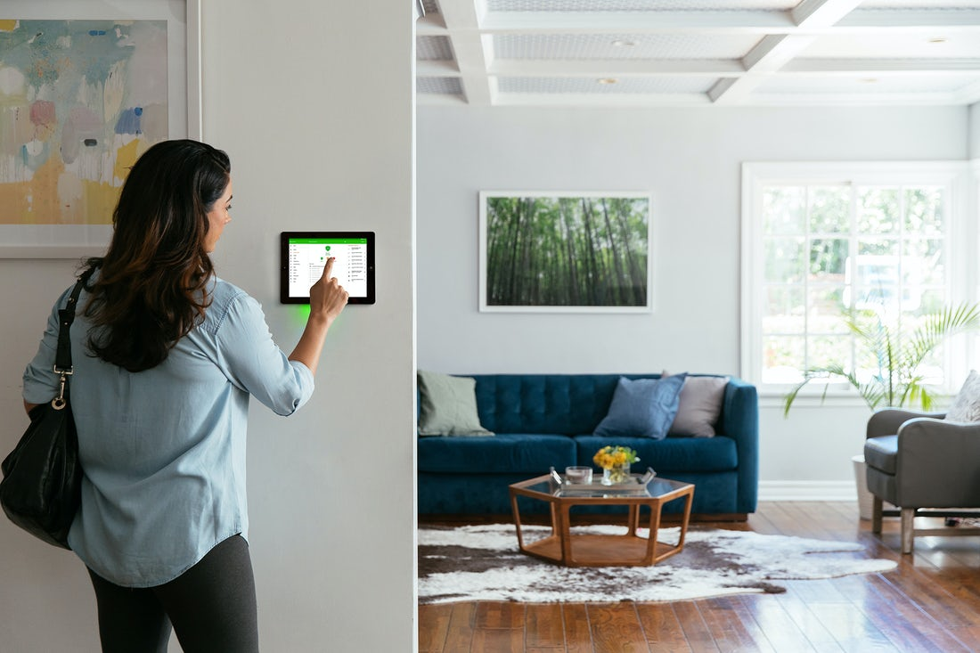 woman-using-smart-home-security-panel-on-the-wall