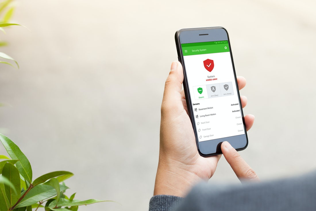 person-holding-smart-phone-with-smart-home-security-system-armed-remotely