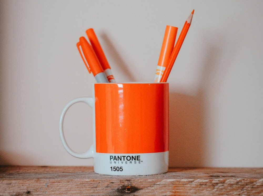 orange pantone cup with pens