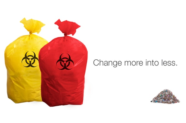 Red and Yellow bags of regulated (biohazardous) medical waste stand beside sterilized shredded waste from Envetec 200 Unit