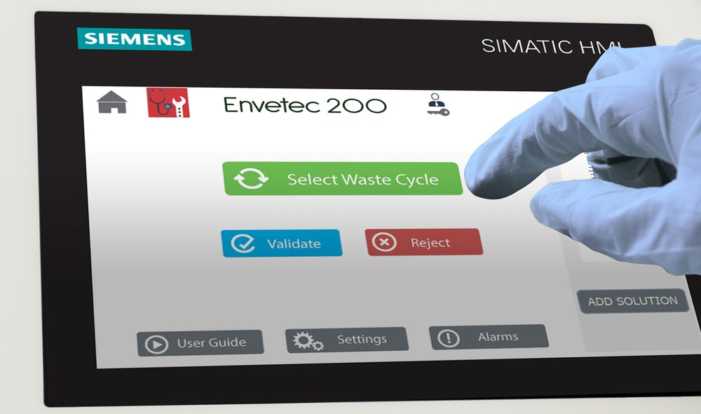 User wearing lab gloves interacts with Envetec touchscreen interface