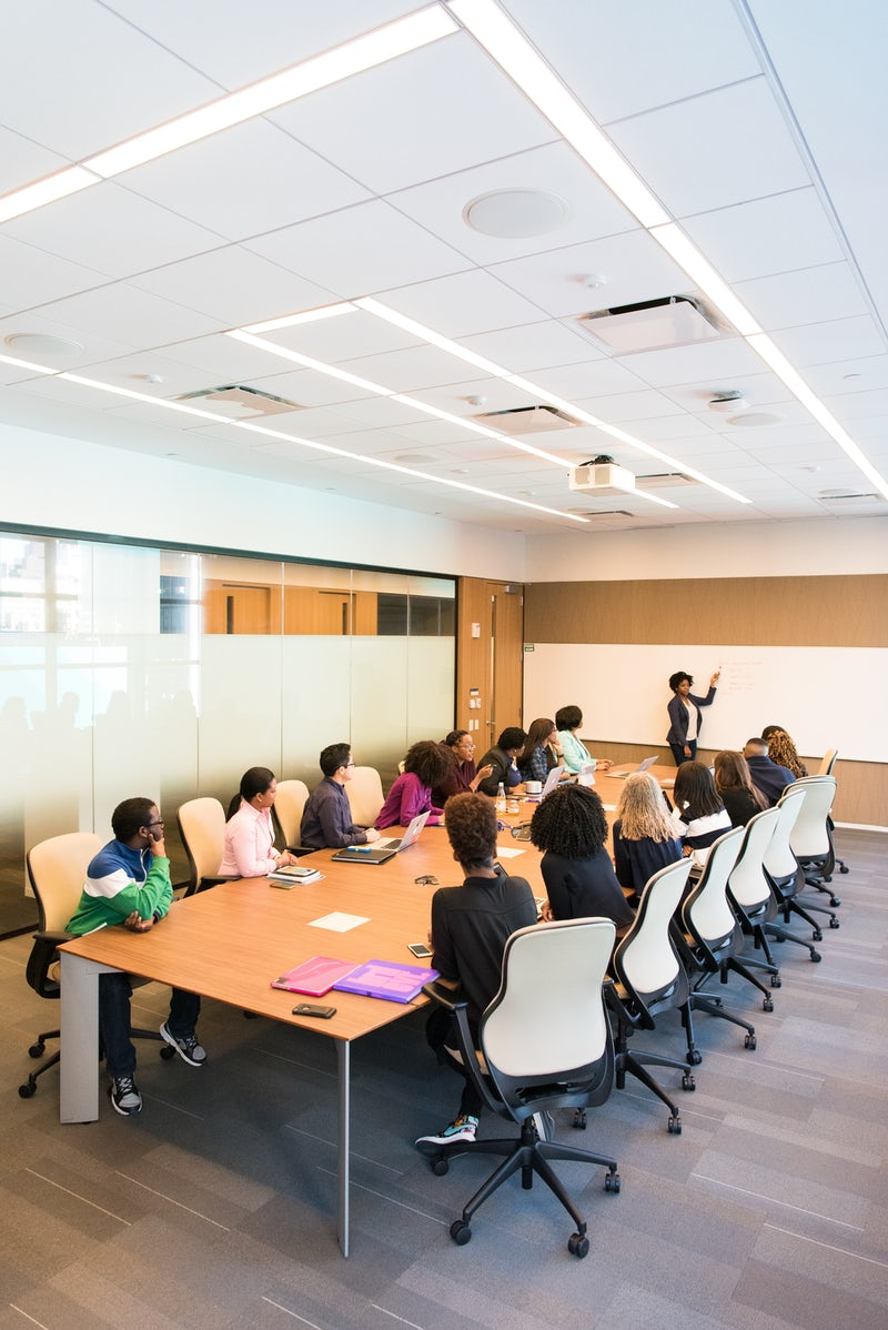 Boardroom with large table fully occupied and speaker presenting at whiteboard at the end of the table
