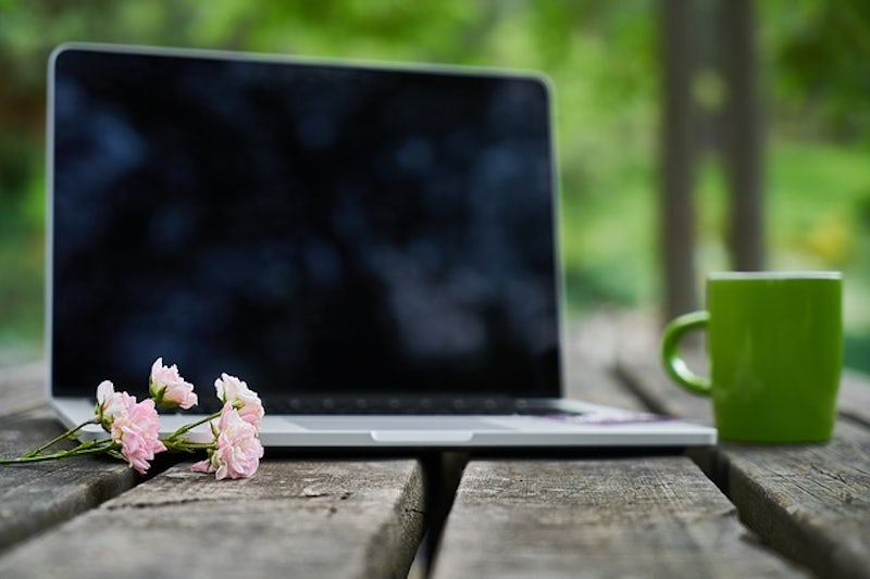 Laptop on bench outside in nature with mug